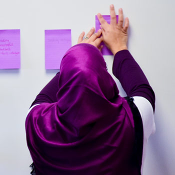 Image of a student putting sticky notes on a white board.