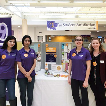 Image of Sarina Wheeler with Laurier students standing at a table